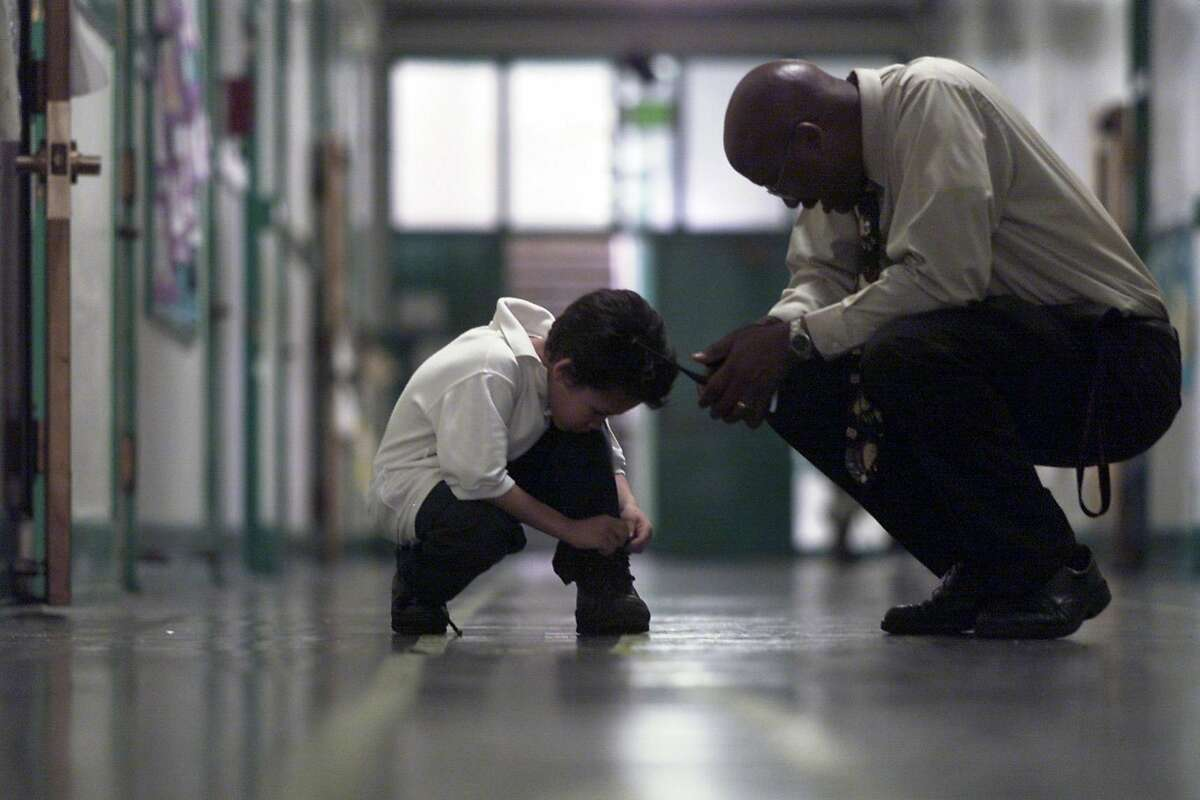 SCHOOLS27A-C-26FEB01-MN-EL Edison's school, San Francisco, Principal Vincent Matthews stops in the hallway to help Guy Gluver,7, 2nd grader tie his shoes. BY ERIC LUSE/THE CHRONICLE