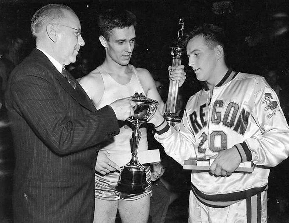 Oregon's Bobby Anet (right) is presented with the first NCAA championship trophy by Big Ten Commissioner John Griffith (left) as Ohio State All American Jimmy Hull watches on March 27, 1939. Photo: Associated Press