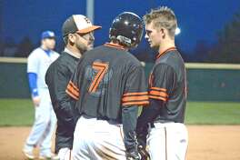 Edwardsville senior Dylan Burris, right, and teammate Kade Burns to EHS coach Tim Funkhouser during Tuesday's game against Wheaton North at Tom Pile Field.