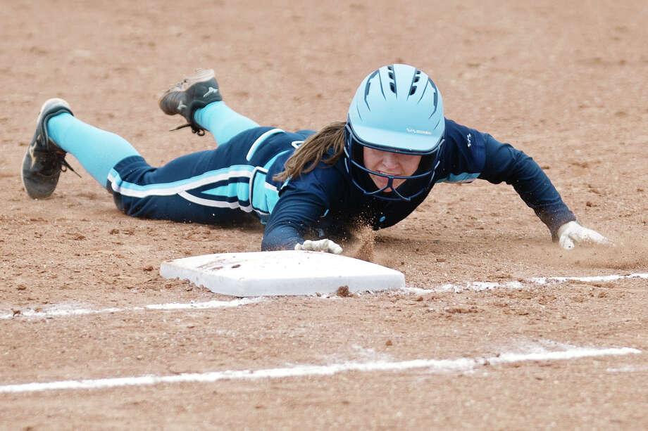Meridian's Kassiday Zmikly slides into first on Wednesday at Meridian High School. Photo: Erin Kirkland/Midland Daily News