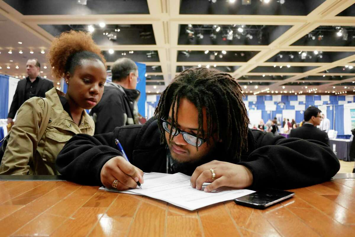 Angelique Porter, left, a career transition readiness coordinator for Glenmont Job Corps works with Job Corps student Jahkeem Garray as he fills out a job application at the 2017 Dr. King Career Fair at the Empire State Plaza Convention Center on Wednesday, March 29, 2017, in Albany, N.Y. (Paul Buckowski / Times Union)