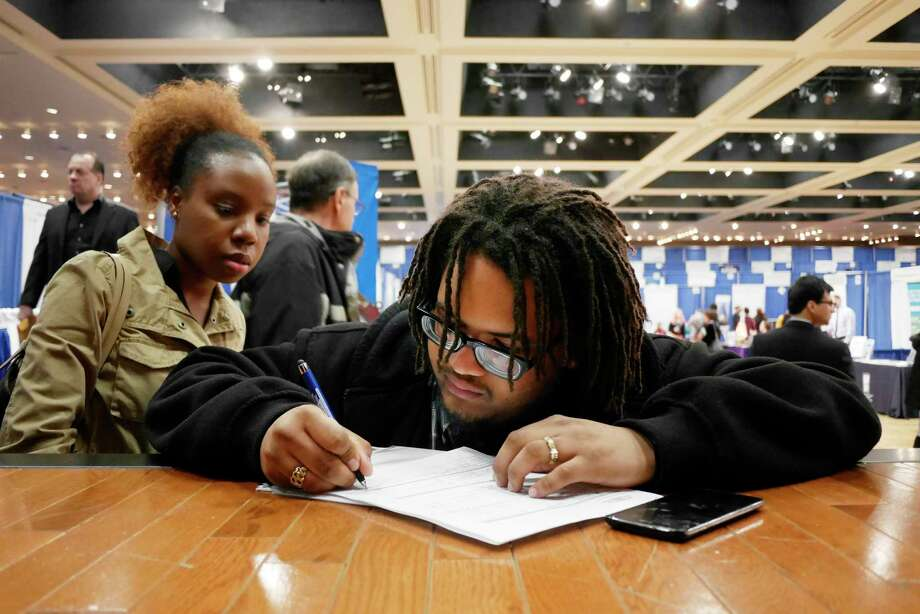 Angelique Porter, left, a career transition readiness coordinator for Glenmont Job Corps works with Job Corps student Jahkeem Garray as he fills out a job application at the 2017 Dr. King Career Fair at the Empire State Plaza Convention Center on Wednesday, March 29, 2017, in Albany, N.Y.  (Paul Buckowski / Times Union) Photo: PAUL BUCKOWSKI / 20040091A