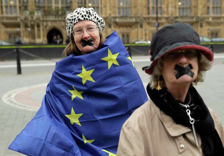 Protesters, stand outside the House of Commons in central London, Wednesday, March 29, 2017. Britain will begin divorce proceedings from the European Union later on March 29, starting the clock on two years of intense political and economic negotiations that will fundamentally change both the nation and its European neighbors. (AP Photo/Matt Dunham)