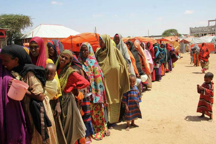 Displaced Somali women stand in line to receive food handouts in a camp outside of Mogadishu, Somalia. (AP Photo/Farah Abdi Warsameh)