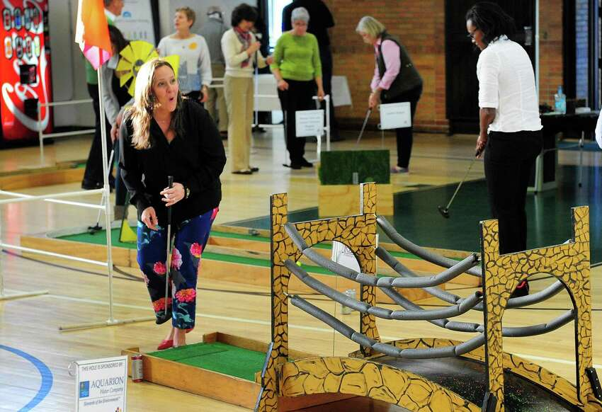 Maureen Funke, representing Gilbaine Building Company in Glastonbury and a board member with Leadership Greater Bridgeport, reacts to almost sinking a hole-in-one during the 3rd Annual McGivney Mini Golf Tournament at the McGivney Community Center on Stillman Street in Bridgeport, Conn. on Wednesday Mar. 29, 2017. Over 160 players signed up to take part in three time slots. Money raised goes towards the after-school programs at the center. Last year the tournament raised about $7000 and the goal this year is for $10,000. Some of the main sponsors included Lanese Construction in Bridgeport and Fairfield County Bank.