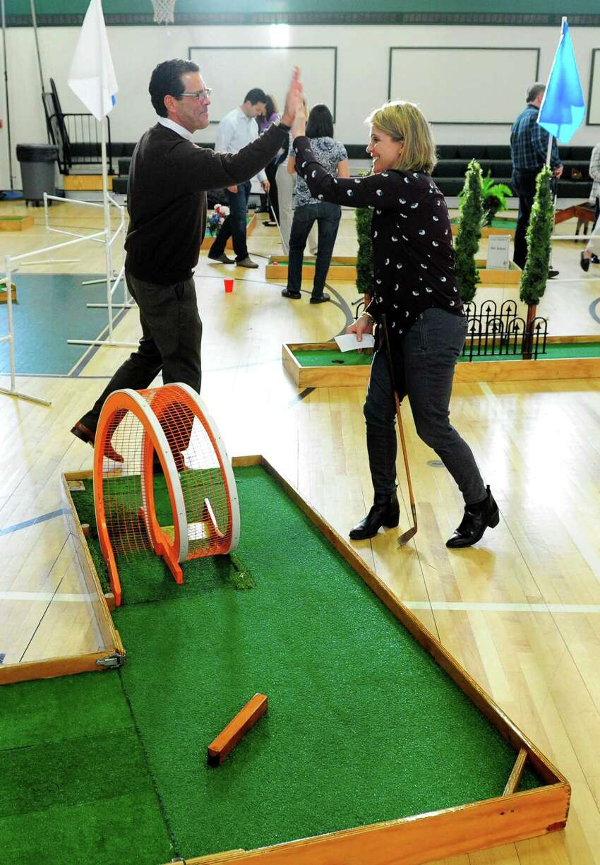 Julia deMeo, with People's United Insurance, gets a high five from teammate Mark Fries after Julia sinks a hole-in-one during the 3rd Annual McGivney Mini Golf Tournament at the McGivney Community Center on Stillman Street in Bridgeport, Conn. on Wednesday Mar. 29, 2017. Over 160 players signed up to take part in three time slots. Money raised goes towards the after-school programs at the center. Last year the tournament raised about $7000 and the goal this year is for $10,000. Some of the main sponsors included Lanese Construction in Bridgeport and Fairfield County Bank.