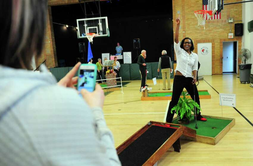 Maria Conlon, with Barnum Financial in Shelton, makes a video of her teammate Ashley Battle as she sinks her putt during the 3rd Annual McGivney Mini Golf Tournament at the McGivney Community Center on Stillman Street in Bridgeport, Conn. on Wednesday Mar. 29, 2017. Over 160 players signed up to take part in three time slots. Money raised goes towards the after-school programs at the center. Last year the tournament raised about $7000 and the goal this year is for $10,000. Some of the main sponsors included Lanese Construction in Bridgeport and Fairfield County Bank.