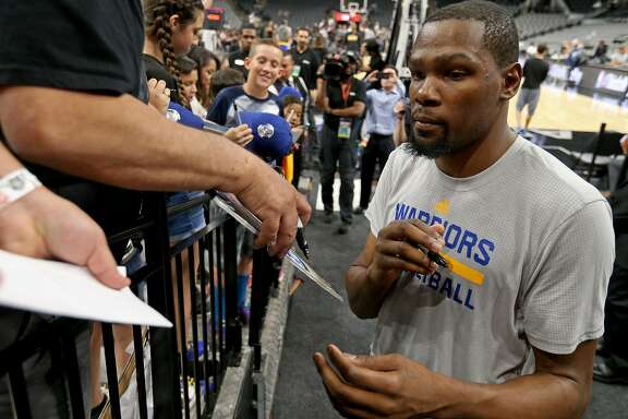 Golden State Warriors' Kevin Durant signs autographs before the game with the San Antonio Spurs Wednesday March 29, 2017 at the AT&T Center.
