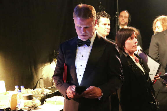 PwC's Brian Cullinan holds envelopes under his arm while using his cellphone backstage last month at the Oscars at the Dolby Theatre in Los Angeles. After the best-picture goof, PwC accountants can't have their cellphones backstage.