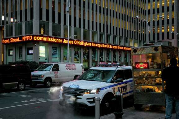 """A news ticker runs outside News Corp.'s headquarters in New York last week during the """"Fox and Friends""""  program. Two black employees of Fox allege that they endured """"relentless"""" hostility related to their race."""