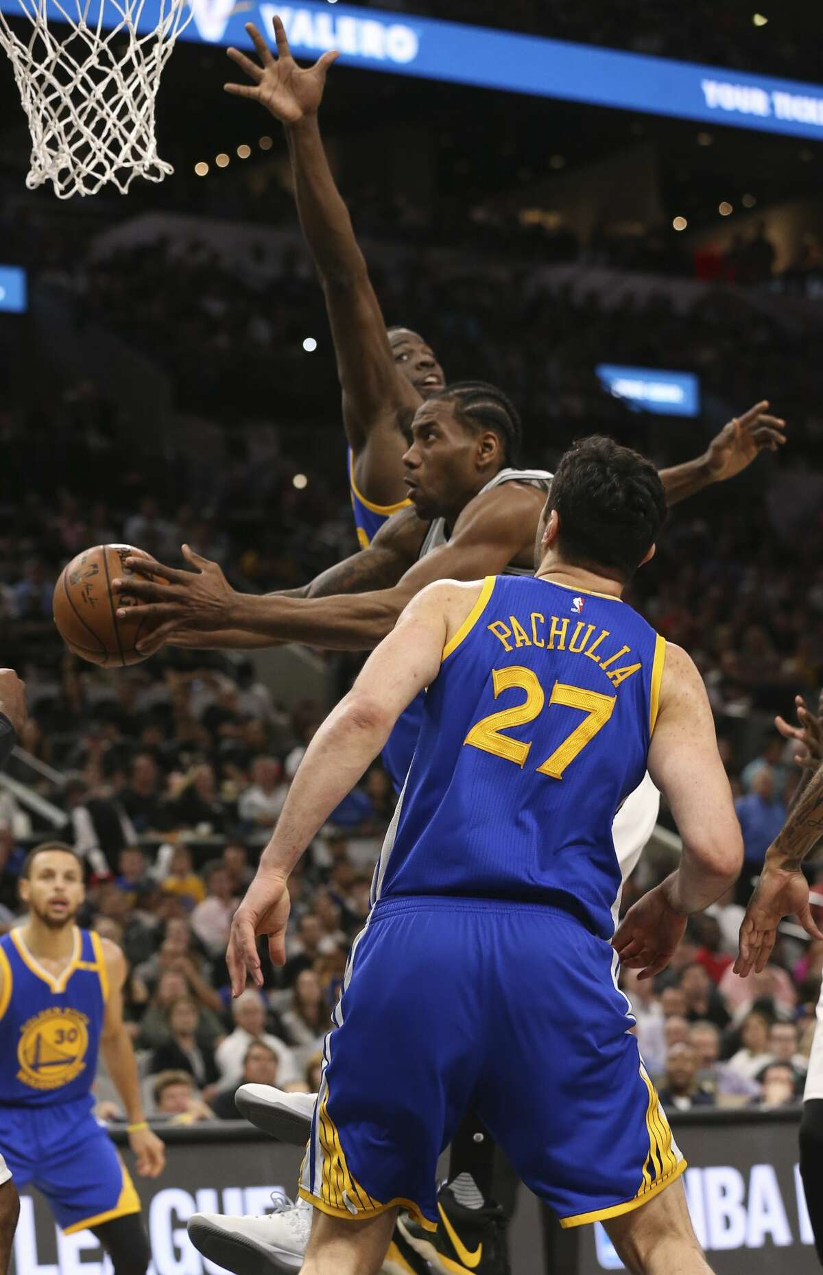 San Antonio Spurs?' Kawhi Leonard drives between Golden State Warriors' Draymond Green and Zaza Pachulia during the first half at the AT&T Center, Wednesday, March 29, 2017.