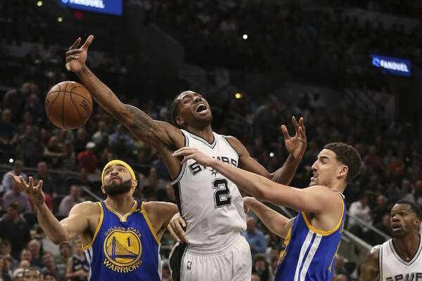 San Antonio Spurs' Kawhi Leonard gets fouled by Golden State Warriors' Klay Thompson, right, as JaVale McGee assists during the first half at the AT&T Center, Wednesday, March 29, 2017.
