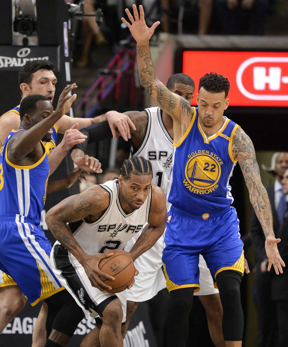 San Antonio Spurs forward Kawhi Leonard (2) looks to pass as he is defended by Golden State Warriors' Matt Barnes (22) and Draymond Green, left, during the first half of an NBA basketball game, Wednesday, March 29, 2017, in San Antonio. (AP Photo/Darren Abate)