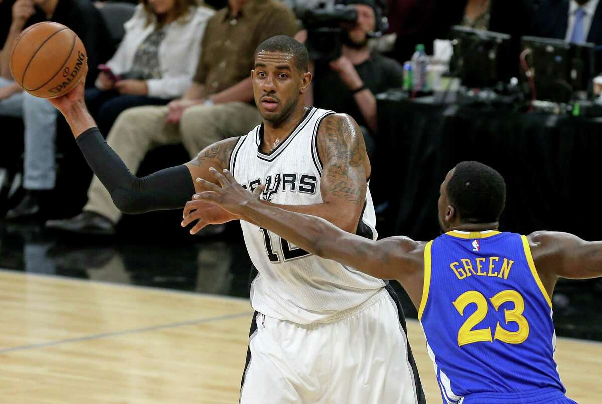 Spurs' LaMarcus Aldridge looks to pass around the Golden State Warriors' Draymond Green during first half action on March 29, 2017 at the AT&T Center.