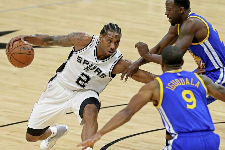 Spurs' Kawhi Leonard looks for room between Golden State Warriors' Andre Iguodala and Draymond Green during first half action on March 29, 2017 at the AT&T Center.