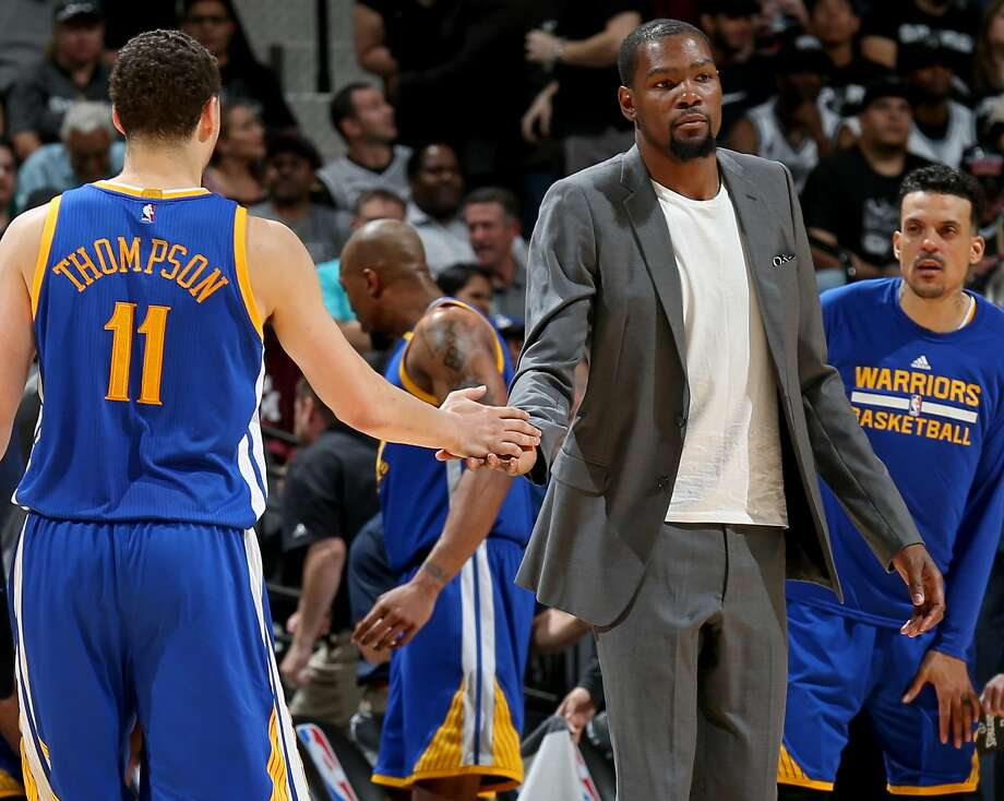 Golden State Warriors' Klay Thompson is greeted by teammate Kevin Durant as he walks to the bench as Matt Barnes looks on during a second half timeout against the San Antonio Spurs Wednesday March 29, 2017 at the AT&T Center. The Warriors won 110-98. Photo: Edward A. Ornelas, San Antonio Express-News