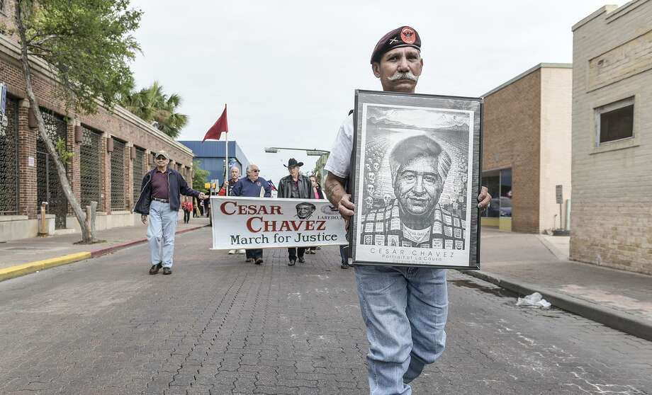 In this March 2016 file photo, Esmeraldo Pruneda holds a poster of Cesar Chavez as he leads a procession down Hidalgo Street during the Cesar Chavez March for Justice. Pruneda was a security guard for Chavez in the 1960s. Photo: Danny Zaragoza, Laredo Morning Times / Laredo Morning Times