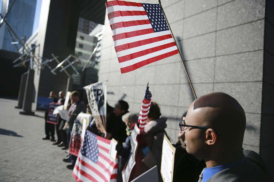 Americans and other expatriates hold banners and U.S. flags near the U.S. Embassy in Tokyo on March 16. Photo: Eugene Hoshiko, Associated Press