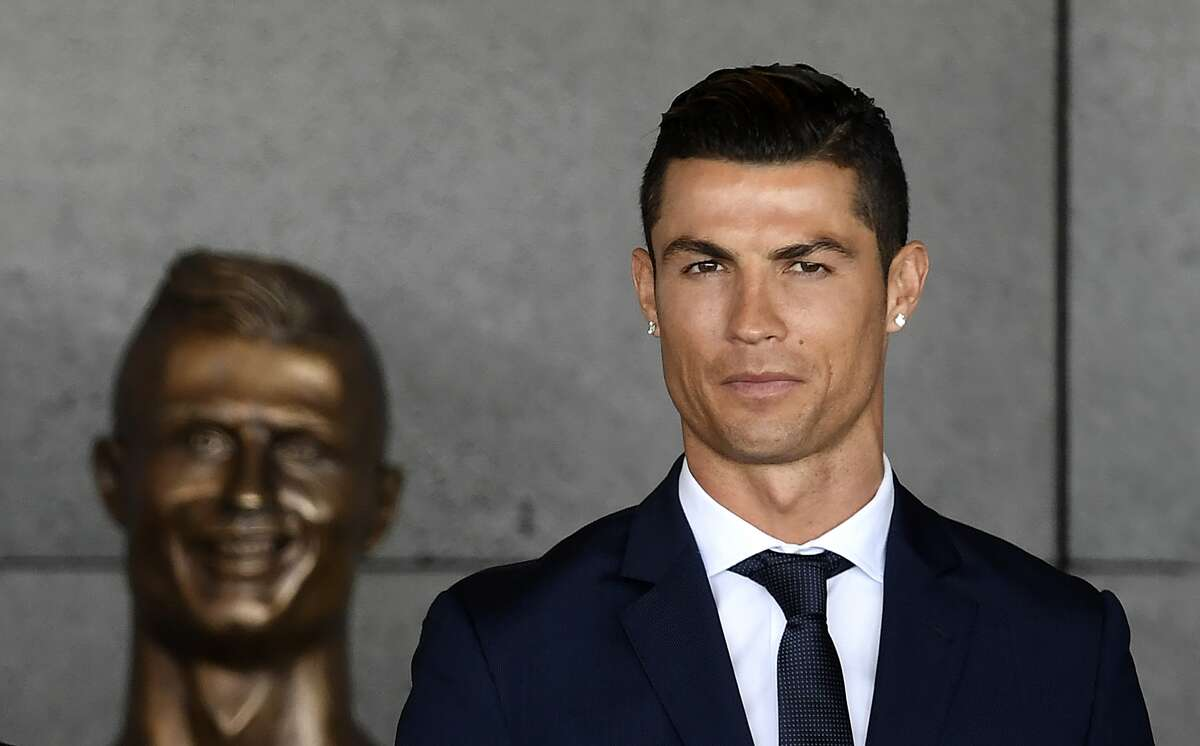 Portuguese footballer Cristiano Ronaldo stands past a bust presented during a ceremony where Madeira's airport in Funchal is to be renamed after Cristiano Ronaldo, on Madeira island, on March 29, 2017. Madeira airport, the birthplace of Portuguese footballer Cristiano Ronaldo, was renamed today in honor of the quadruple Ballon d'or and captain of the Portuguese team sacred European champion last summer.