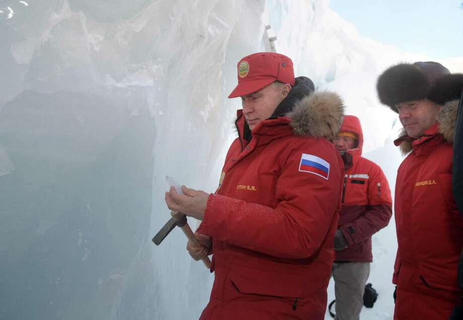 Russian President Vladimir Putin (left) and Prime Minister Dmitry Medvedev inspect a cavity in a glacier on the Franz Josef Land archipelago in Arctic Russia. Photo: Alexei Druzhinin /Associated Press / POOL SPUTNIK KREMLIN