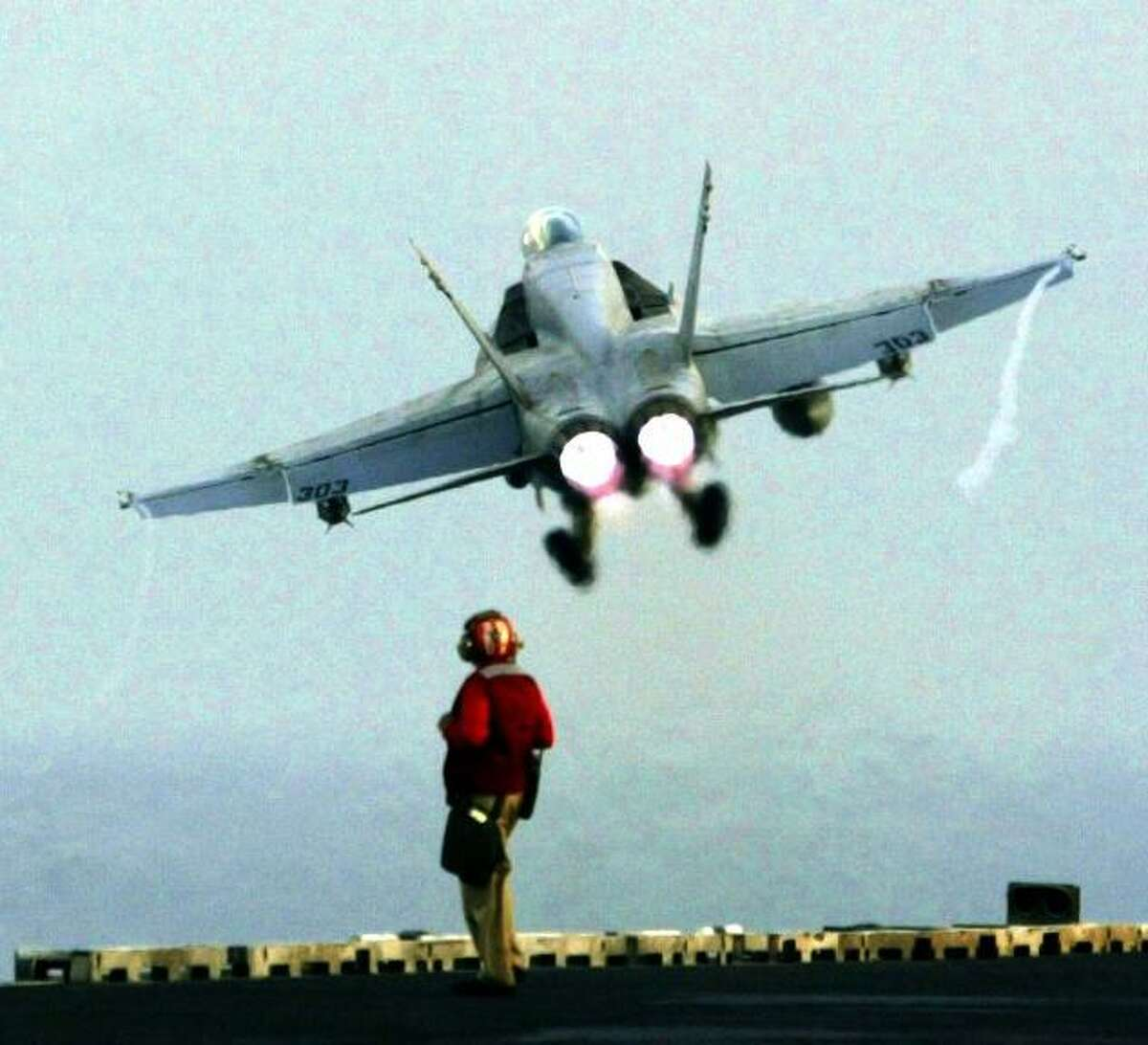 ABOARD THE AIRCRAFT CARRIER USS ABRAHAM LINCOLN (NIMITZ-CLASS) IN THE PERSIAN GULF. 3/17/2003 A flight deck weapons handler watches a F/A-18 Hornet leave the ship Wednesday afternoon. Photo by Grant M. Haller/Seattle P-I/Hearst Newspapers 3/17/2003