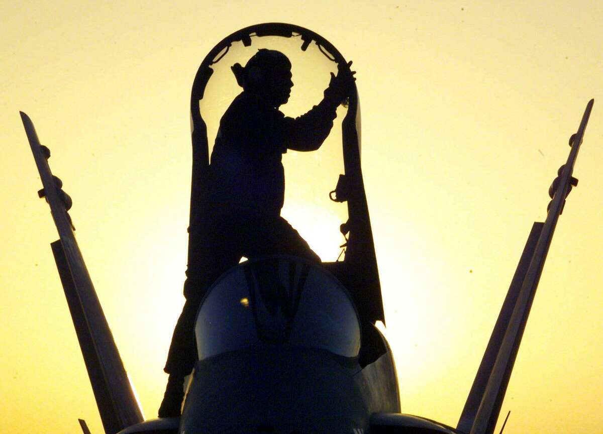 An unidentified aircraft captain cleans the canopy of an F18 warplane at sunset on board the aircraft carrier the USS Enterprise, ahead of sorties over Iraq on the second day of bombing by US and British forces Friday December 18, 1998. (AP Photo/Louisa Buller).
