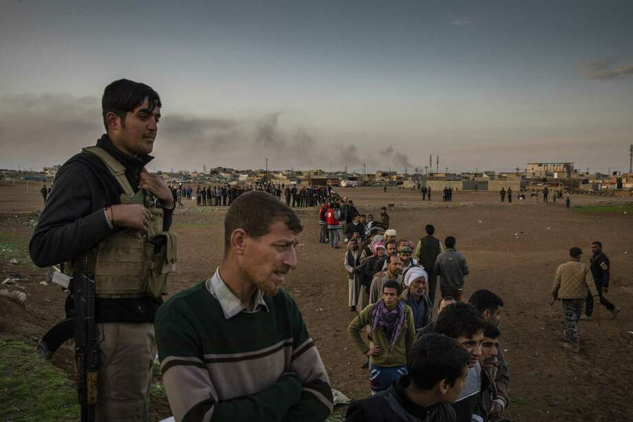 FILE — Civilians wait for aid in Mosul, Iraq, in the midst of an offensive to take the city back from the Islamic State group, March 13, 2017. From Syria and Yemen to Mosul, where airstrikes killed dozens of people on March 17, the United States military is deepening its involvement in a string of complex wars, ones lacking clear endgames. (Ivor Prickett/The New York Times) Photo: IVOR PRICKETT, STR / NYT / NYTNS