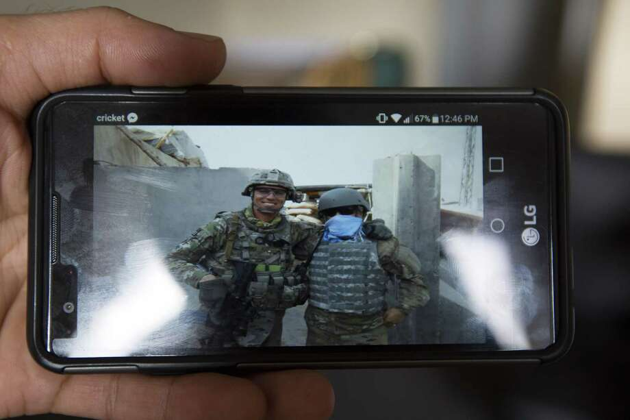 Samir Kohistani shows a picture of himself and a U.S. Army soldier he worked with as a translator in his native Afghanistan, Monday, Nov. 28, 2016, in Houston. He had to hide his identity when working because of the danger associated with his job. After earning his legal entry to the United States, Kohistani is now living in an apartment with several other former translators and working at a print shop. Kohistani is hoping to either study to be a nurse or join the U.S. Army in order to give back to the country he says gave so much to him. ( Mark Mulligan / Houston Chronicle ) Photo: Mark Mulligan, Staff / Houston Chronicle / Stratford Booster Club