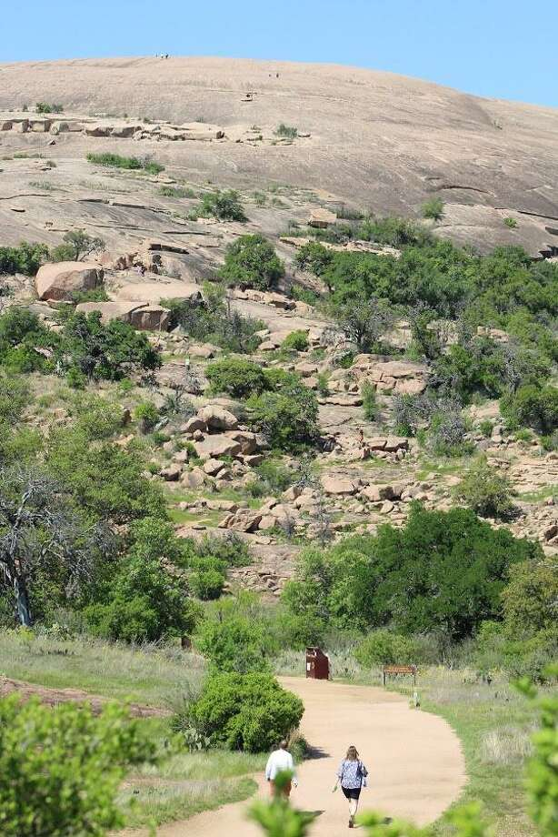Hikers begin their ascent on Enchanted Rock through the entrance of the frequently hiked Summit Trail. Photo: Jakob Lopez /For The Express-News