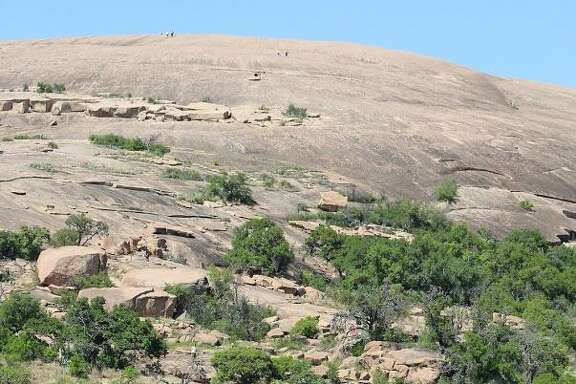 Hikers begin their ascent on Enchanted Rock through the entrance of the frequently hiked Summit Trail.