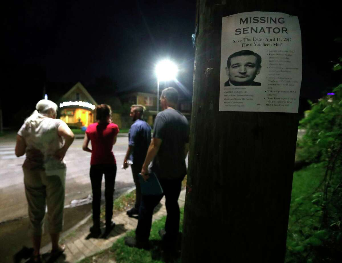 """Houstonians walk under the cover of darkness to put up """"Ted Cruz is missing"""" fliers up around a Montrose neighborhood, Wednesday, March 29, 2017, in Houston. The fliers are catching people's attention, ahead of an upcoming """"Ted Cruz Is Missing"""" town hall meeting."""