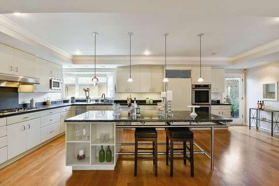 The kitchen features dual ovens and a quartet of pendant lights.�