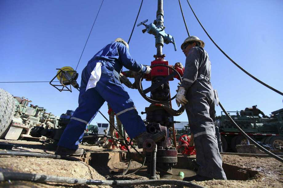 Oil field workers for Pioneer Natural Resources help frack a well in an oil field south of Midland. Photo: New York Times /File Photo / NYTNS
