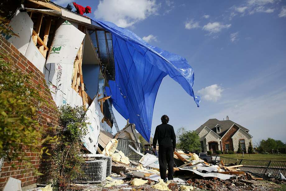 John Hampton stands outside his brother's house that was damaged by a powerful storm in Rockwall, Texas, on Wednesday. Photo: Rose Baca, Associated Press