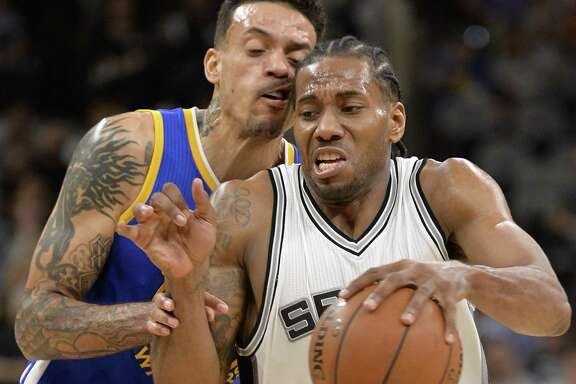 Spurs forward Kawhi Leonard drives against Golden State Warriors forward Matt Barnes during the second half on March 29, 2017, in San Antonio. Golden State won 110-98.