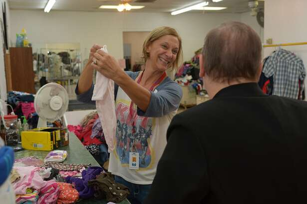 Kim Hogan, left, chats with Cypress Assistance Ministries Executive Director Martha Burnes, right, as she sorts baby clothes in the cellar of the Angels' Attic resale shop on Oct. 22, 2015. (Photo by Jerry Baker/Freelance)