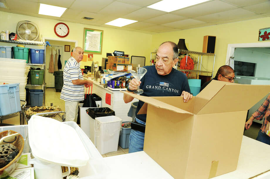Tito Sessarego, front, helps to sort donated merchandise along with Dave Barstow, back left, and Francisco Navarro at Cypress Assistance Ministries. Photo: Tony Gaines, Photo