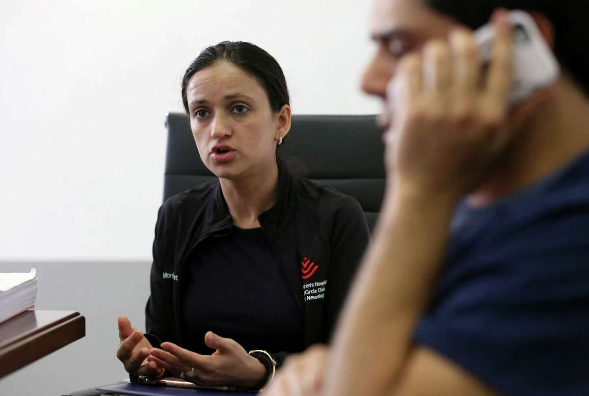 Doctor Monika Ummat, center, talks about the details of their case while her husband Pankaj Satija, foreground, talks on the phone during a press conference at the Quan Law Group offices Thursday, March 30, 2017, in Houston. Satijaand Ummat are facing possible immediate return to India.