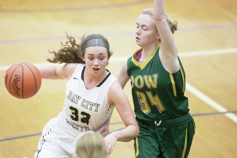 THEOPHIL SYSLO | For the Daily News Bay City Western's McKenna Walker drives past Dow High's Paige Messick during last season's girls' basketball Class A district final at Saginaw Heritage High School.