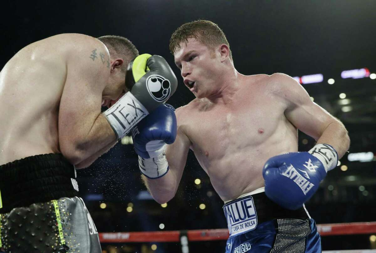 Canelo Alvarez (right) punches Liam Smith fight during the WBO junior middleweight championship boxing match at AT&T Stadium in Arlington on Sept. 17, 2016.