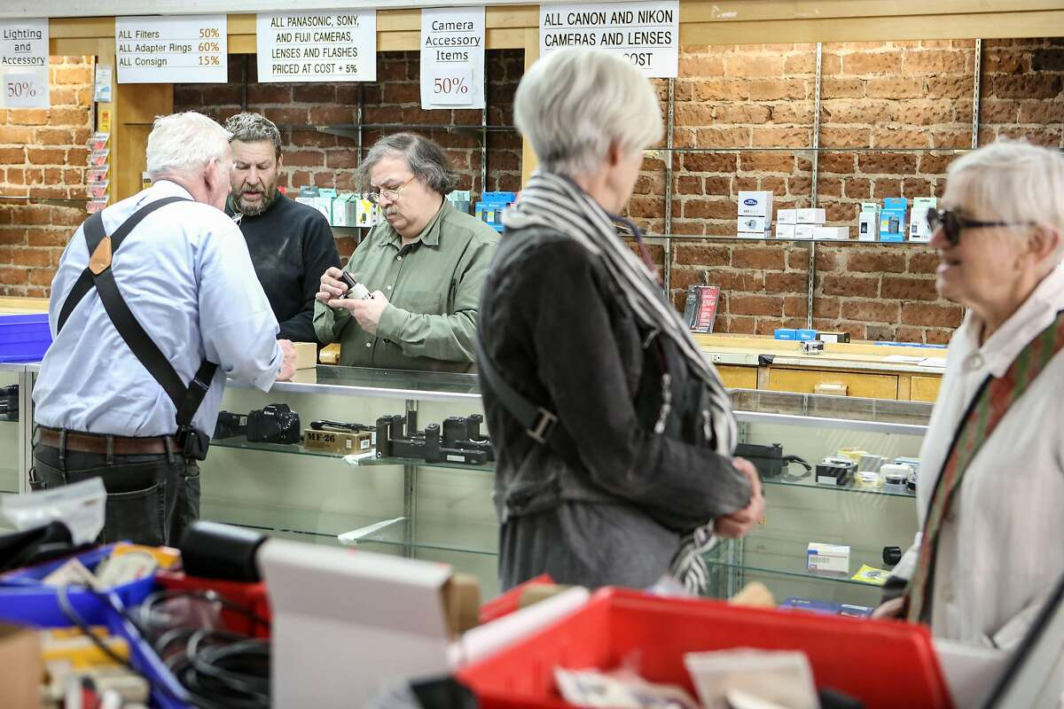 """John Gasser (left) looks over a piece of equipment with """"Max"""" (center) and Alex Carrillo while customers look around at Adolph Gasser on Thursday, March 30, 2017 in San Francisco, Calif."""