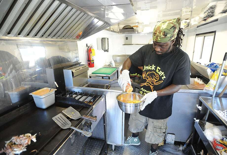 Jaylen Lewis seasons fries at Unick Eat'z on Washington Boulevard and Houston Street Thursday. The mobile truck offers a range of finger foods ranging from burgers to Mexican food. Photo taken Thursday, October 6, 2016 Guiseppe Barranco/The Enterprise Photo: Guiseppe Barranco