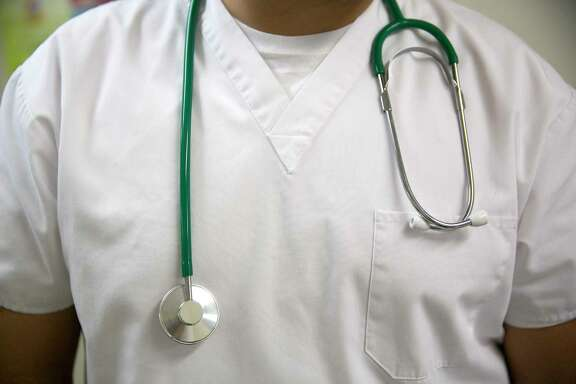 A stethoscope hangs around the neck of a medical assistant in this arranged photograph at a Community Clinic Inc. health center in Silver Spring, Maryland, U.S., on Tuesday, Oct. 1, 2013. Government-run health insurance exchanges, the cornerstone of the 2010 Affordable Care Act, opened their doors today for sales of subsidized bronze, silver, gold or platinum policies, with correspondingly higher costs. Coverage begins in January and enrollment lasts through March 2014. Photographer: Andrew Harrer/Bloomberg