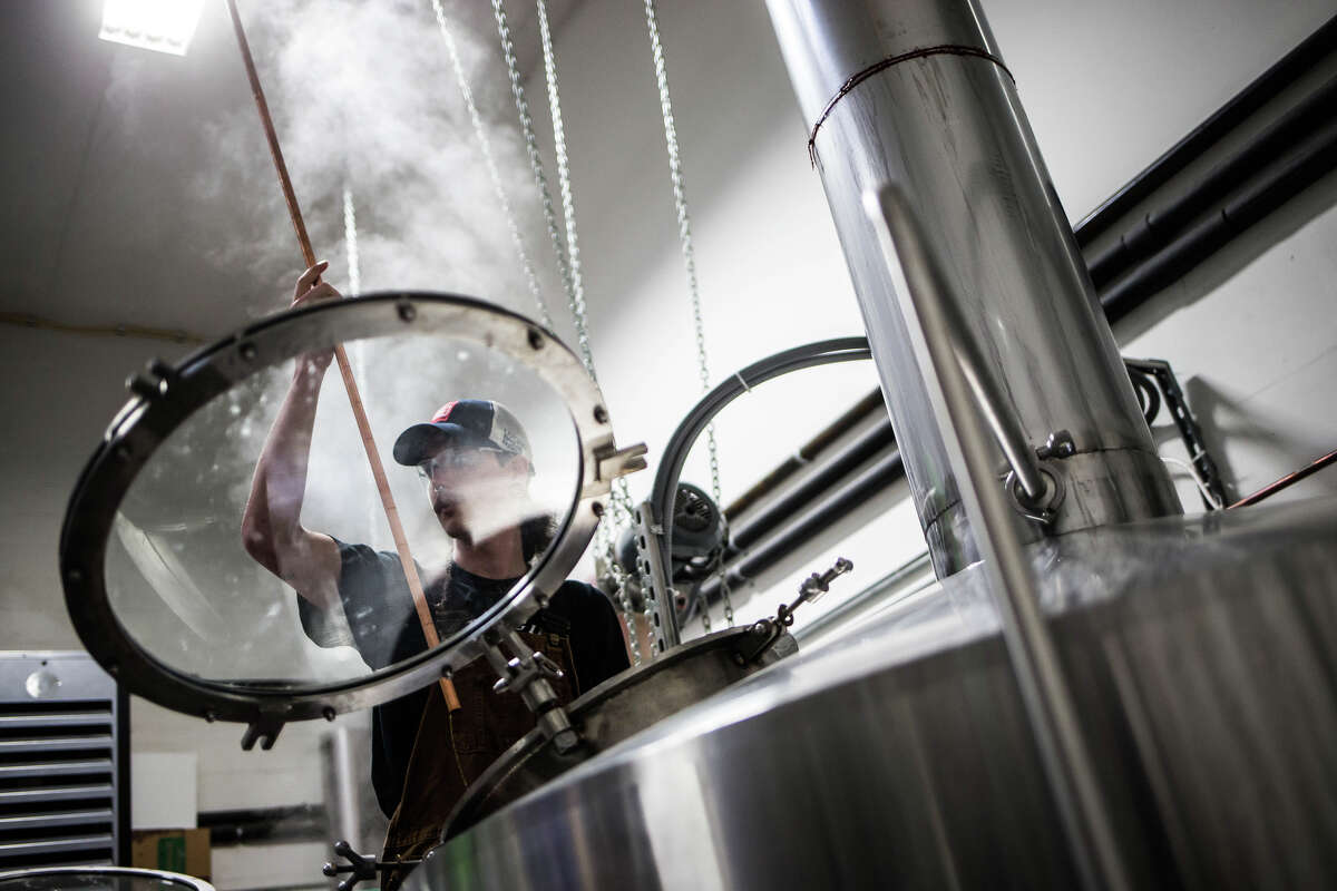 Assistant brewer Josh Yoker checks the wort for the Beardless Brewer Red at Lucky Envelope Brewing in Ballard on Tuesday, March 28, 2017. (GRANT HINDSLEY, seattlepi.com)
