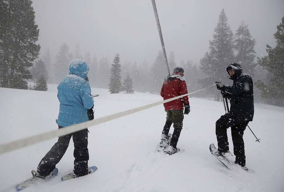 Nic Enstice (right) pulls a tape measure alongside Frank Gehrke (center), chief of the snow survey pro gram for the Department of Water Resources, while sampling the snowpack at Phillips Station in the High Sierra. Photo: Justin Sullivan / Photos By Justin Sullivan / Getty Images / 2017 Getty Images
