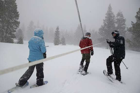 Nic Enstice (right) pulls a tape measure alongside Frank Gehrke (center), chief of the snow survey pro gram for the Department of Water Resources, while sampling the snowpack at Phillips Station in the High Sierra.