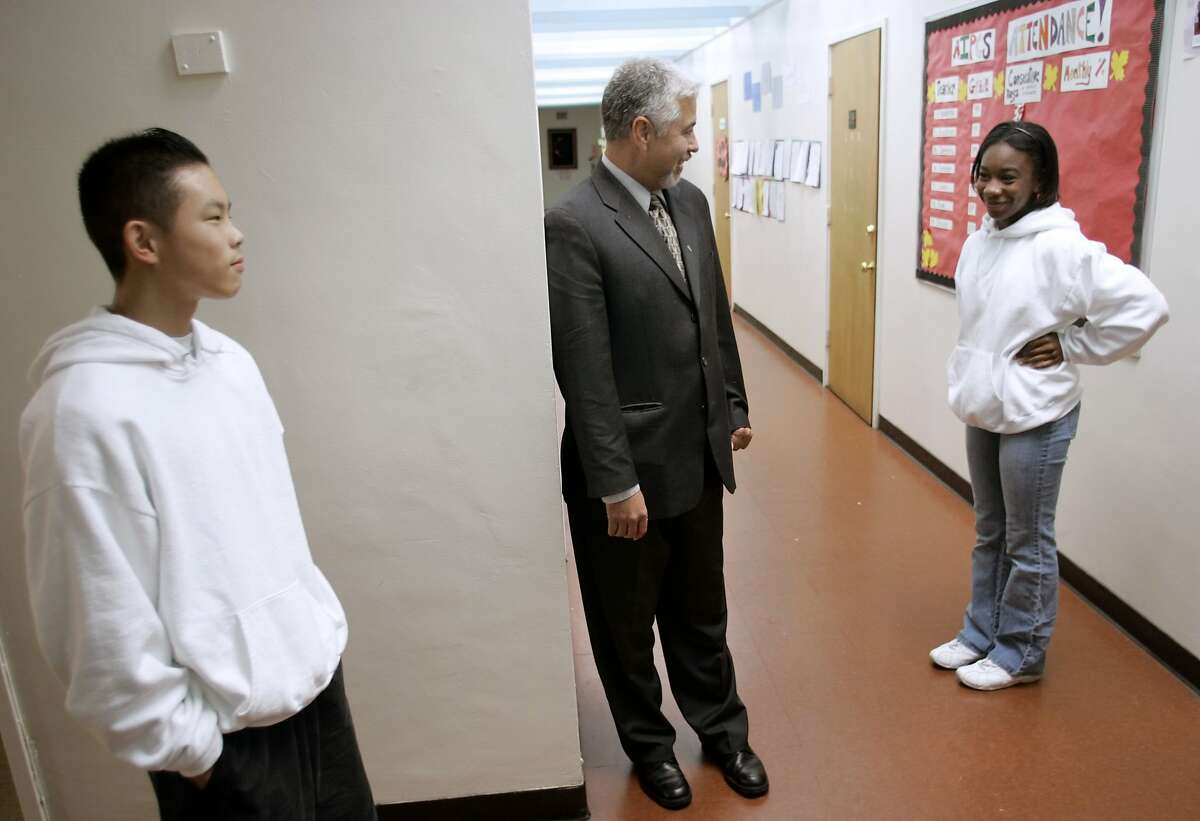 AICHARTER30_003_CAG.JPG Dr. Ben Chavis, center, principal of American Indian Charter School, speaks with students, Dominique Collins, right, and Kevin Lee, in the school hallway before lunch on Tuesday, November 29, 2005. American Indian Charter School is one of Oakland school district's top ranked middle schools. On the brink of failure five years ago, Dr. Ben Chavis took over and has turned the school around with unorthodox disciplinary tactics and a strong emphasis on academics. He gives merit pay to both students and teachers for perfect attendence and uses public humiliation to discipline students for breaking rules. His teachers are not credentialed and he doesn't believe in technology or arts in education. The board will consider a charter next month to allow Chavis to open up a high school as well. Photo by Carlos Avila Gonzalez / The San Francisco Chronicle Photo taken on 11/29/05 in Oakland, CA. Ran on: 12-16-2005 American Indian Public Charter School test scores are higher than any other Oakland middle schools. Ran on: 12-16-2005 American Indian Public Charter School test scores are higher than any other Oakland middle schools.