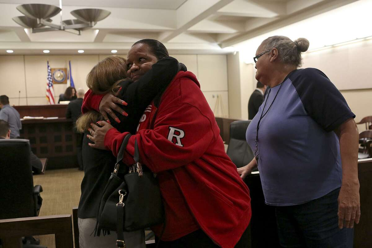 Olivia Fenner, center, the mother of Tru Trusty, who was 16 at the time of his murder on Sept. 26, 2015, embraces prosecutor Catherine Hayes as Fenner's sister, Charlotte, stands by after Dominique Bailey was sentenced to 30 years in prison after taking a plea deal for the charge of murder in the 144th Criminal District Court on Thursday, March 30, 2017.
