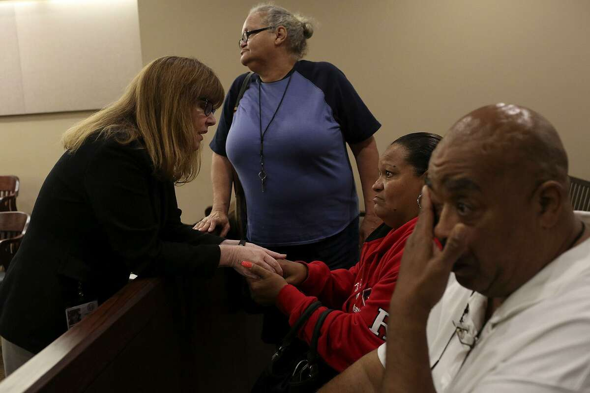 Olivia Fenner, center, the mother of Tru Trusty, who was 16 at the time of his murder on Sept. 26, 2015, talks with prosecutor Catherine Hayes as Fenner's sister, Charlotte, stands by and Trusty's father, Joseph Trusty, right, wipes his tears after Dominique Bailey was sentenced to 30 years in prison after taking a plea deal for murder in the 144th Criminal District Court on Thursday, March 30, 2017.