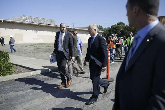 Governor Jerry Brown (right) talks with Gareth Lacy (left), deputy press secretary, after speaking at a press conference announcing a transportation investment package to fix roads, freeways and bridges across California and invest more toward transit and safety on Thursday, March 30, 2017 in Concord, Calif.